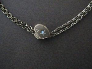 Alkuperäinen Amanda Vuorelle kuulunut koru on valmistettu pronssista. Kaksinkertaisiin ketjuihin on kiinnitetty sydämenmuotoinen riipus, jossa on pieni sininen lasihelmi ja kaiverruksia.